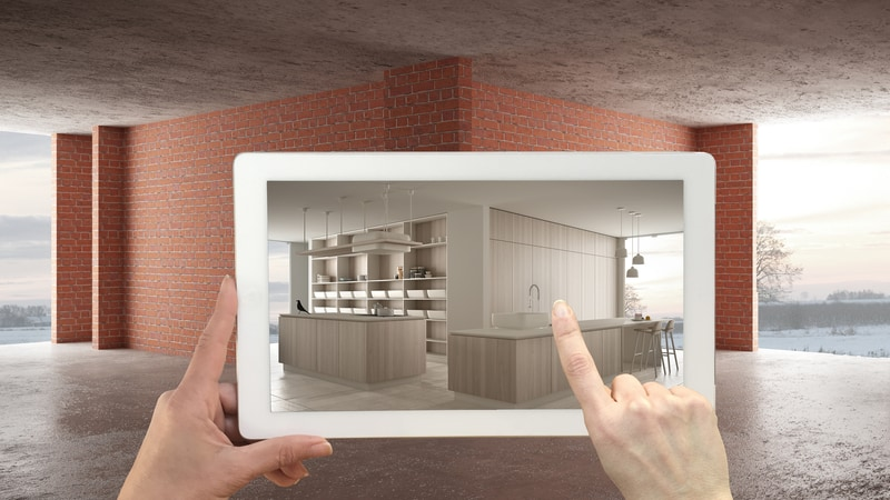 A Picture Of A Tablet Being Held Up To A Blank, Corner Background Setting. The Tablet, However, Is Showing Furniture Instead Of The Blank Canvas - Which Is Showcasing Augmented Reality.